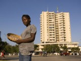 Girl Selling Peanuts on Metical Square, with Highrise Building Behind, Beira, Sofala, Mozambique - Ariadne Van Zandbergen