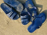 Blue Plastic Sandals, Covered in Sand, Lie on a Beach in Hong Kong