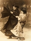 Elderly Priest and Young Woman Trying to Hold on to an Umbrella Turned Inside-Out by a Gust of Wind