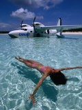 Female Floating in Crystal Waters in Front of Seaplane, Bahamas - Greg Johnston