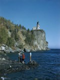 Tourists Stand on Rocky Shoreline Looking Up at Lighthouse Atop Cliff - Jack Fletcher