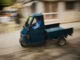 Three Wheeled Vehicle known as an Ape Speeds By - James Braund