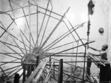 Boy Working a Very Large Spinning Wheel - James Burke