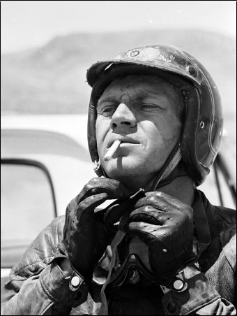 actor steve mcqueen putting on helmet during 500 mi. Black Bedroom Furniture Sets. Home Design Ideas