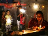 A Woman Lights Earthen Lamps as Children Ignite Firecrackers in New Delhi - Manish Swarup