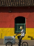 Ice Cream Vendor Riding Bicycle Past Colourful House, Granada, Nicaragua - Margie Politzer