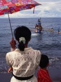 Woman with an Umbrella Watches a Boat Delivering Ashes to the Sea, Bali, Indonesia - Margie Politzer