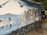 Mural Painting of People and Wildlife Near a Sidewalk Cafe