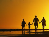 A Family Holding Hands is Silhouetted against the Setting Sun - Rich Reid
