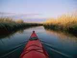 The Bow of a Kayak Leads the Way Through a Marsh Channel - Skip Brown