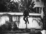 Man in a Suit and Bowler Hat Jumping in the Air in a Backyard in Brooklyn, Ny - Wallace G. Levison
